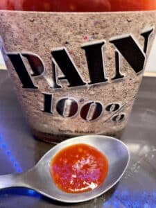 Pain 100% Hot Sauce on a spoon